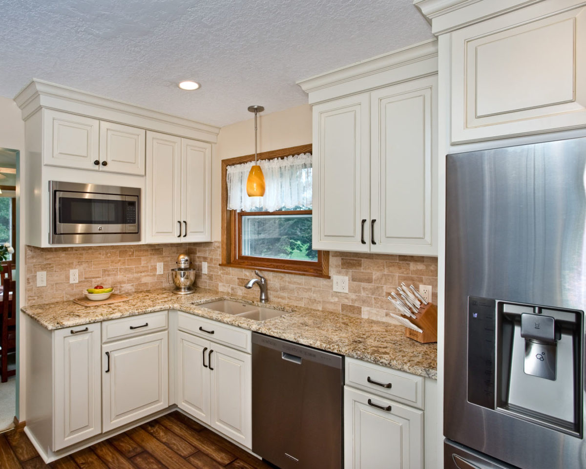 White kitchen with undermount sink, luxury vinyl floor and stainless appliances