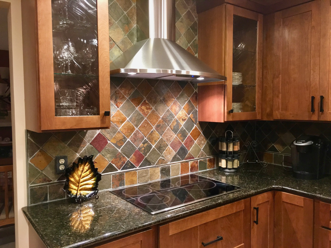 Induction cooktop with stainless hood and slate tile backsplash