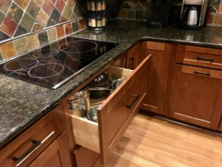 Deep pull-out drawers under induction cooktop in cherry kitchen