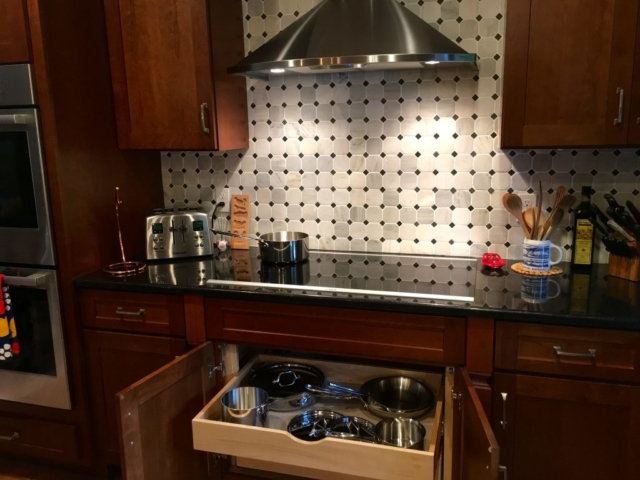 Induction cooktop with ceiling height tile backsplash and stainless hood